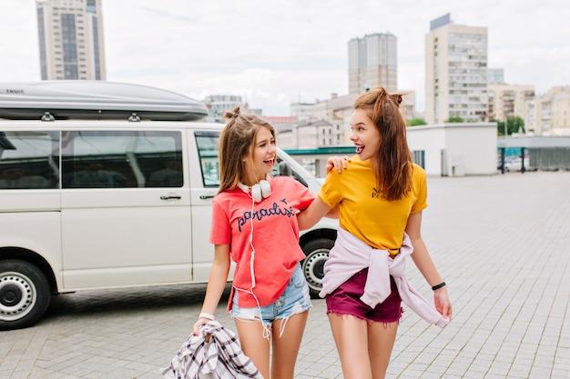 興奮した二人の女の子が車で四角に来て、笑顔でお互いを見つめながら歩いている