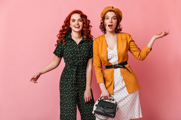 Two excited girls gesturing while looking at camera. curly french woman posing with friend on pink background.