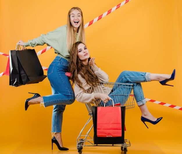 Two excited happy girls have cart with colorful shopping bags and signal tape isolated over yellow