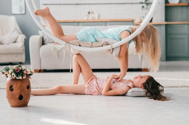 2人の興奮したモデルの女の子は、室内で楽しい時を過します。それの上に横たわる彼女の友人とスイングの下で横になっているピンクのドレスの美しい少女。