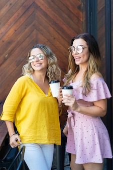 Two excited stylish girlfriends drinking coffee in cafe