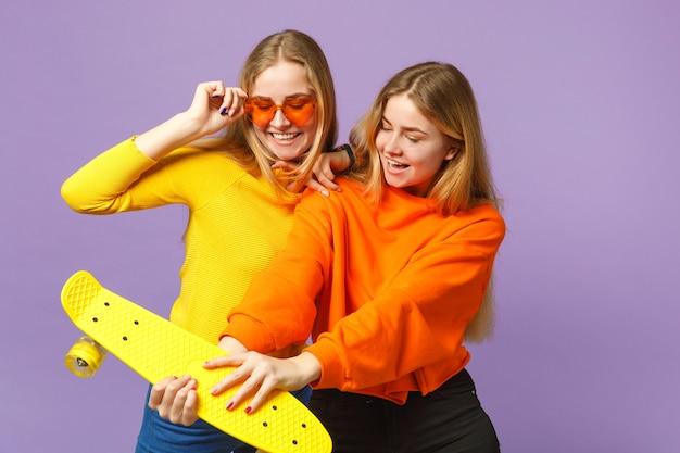 鮮やかな服を着た2人の興奮した若い金髪の双子の姉妹の女の子、ハートの眼鏡はパステルバイオレットブルーの壁に分離された黄色のスケートボードを保持します。人々の家族のライフスタイルの概念。