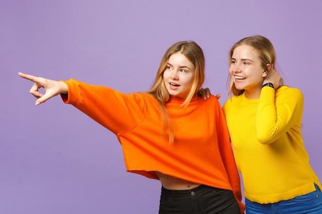 パステルバイオレットブルーの壁に隔離された人差し指を脇に向けて鮮やかなカラフルな服を着た2人の興奮した若いブロンドの双子の姉妹の女の子。人々の家族のライフスタイルの概念。