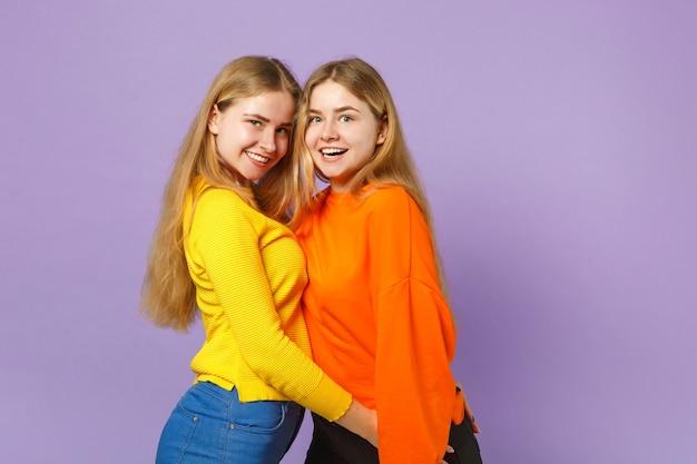 두 흥분된 젊은 금발 쌍둥이 자매 소녀 서, 파스텔 바이올렛 파란색 벽에 고립 된 생생한 화려한 옷을 입고. 사람들이 가족 라이프 스타일 개념.