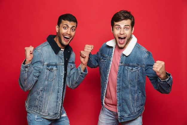 Двое возбужденных друзей молодых людей в джинсовых куртках стоят изолированно над красной стеной и празднуют