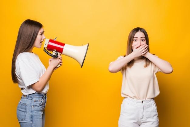 Две возбужденные молодые женщины-подруги в повседневных футболках, джинсовой одежде, позируют изолированно на желтой стене. концепция образа жизни людей. копируйте пространство для копирования. крик в мегафон, разводя руками
