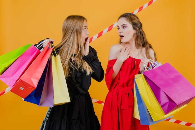 Two excited young women with colorful shopping bags and signal tape isolated over yellow