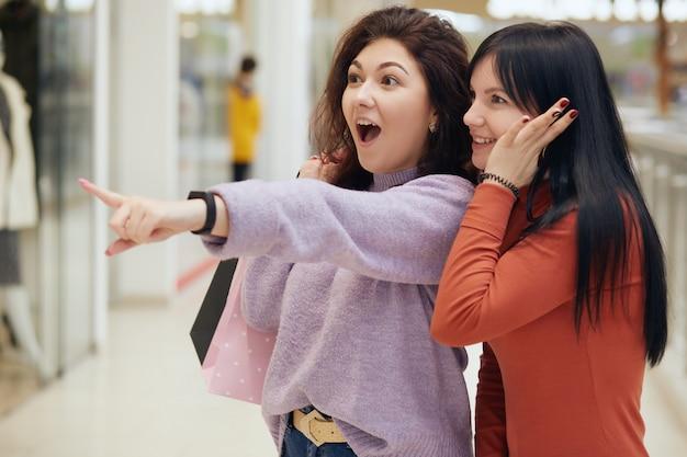 叫んで、感情的に話している買い物袋を持つ2つの興奮した若い女性