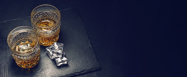 Two expensive glasses of whiskey with ice on a black stone tray