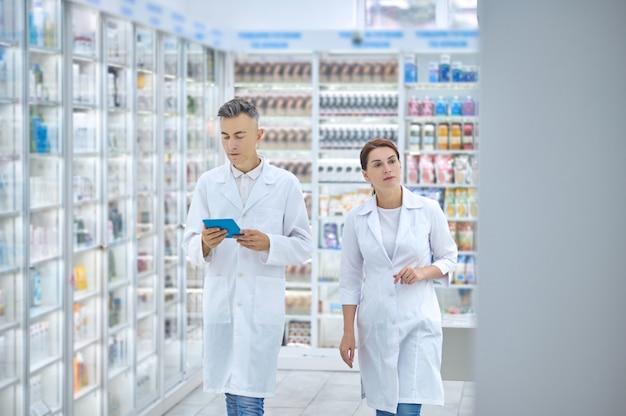 약국 창고에서 약을 검사하는 두 명의 전문 약사