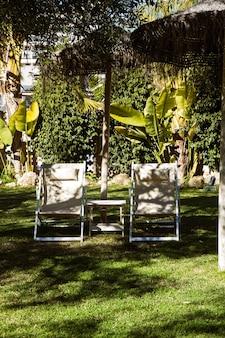 밀짚 우산 아래 두 개의 패브릭 정원 의자