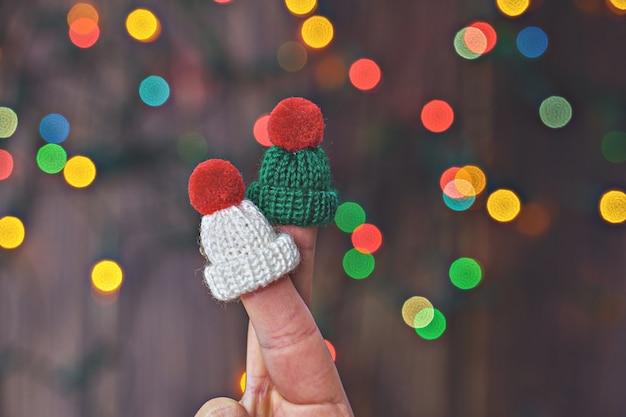クリスマスライトの背景の上のニット帽子の2つの顔のないロマンチックなカップルの指