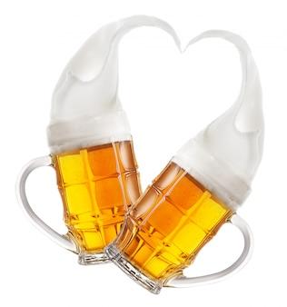 심장의 모양에 거품의 밝아진 맥주 두면 처리 된 머그잔 프리미엄 사진