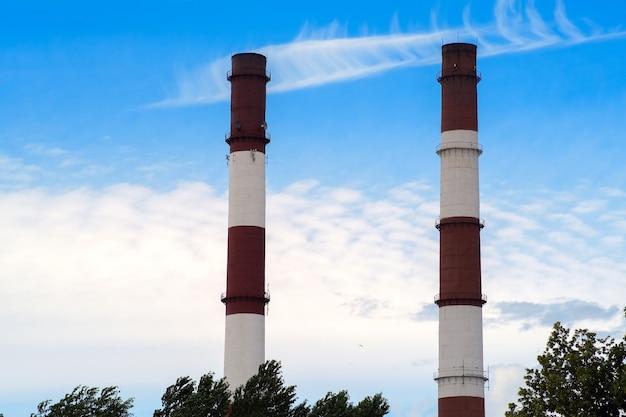 푸른 하늘에 대 한 두 개의 공장 굴뚝입니다. 연기 배출은 독성 기준을 초과하여 검사를 통해 중단되었습니다.