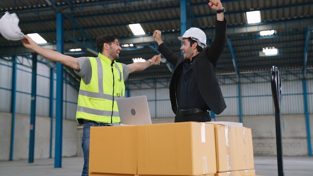 Two factory worker celebrate success together in the factory or warehouse