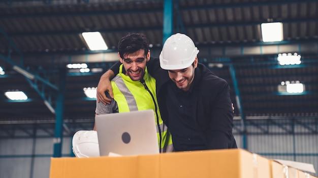 두 공장 노동자가 공장이나 창고에서 함께 성공을 축하합니다.