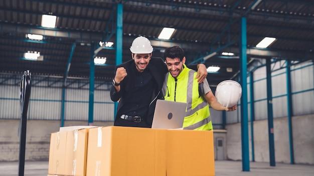 2人の工場労働者が工場または倉庫で一緒に成功を祝う