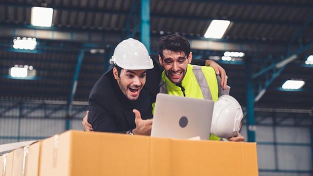 Два заводских рабочих вместе празднуют успех на заводе