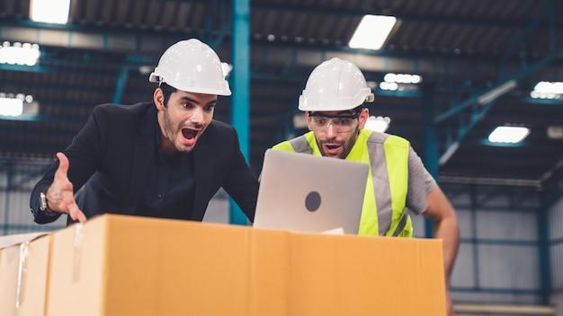 2人の工場労働者が工場で一緒に成功を祝う