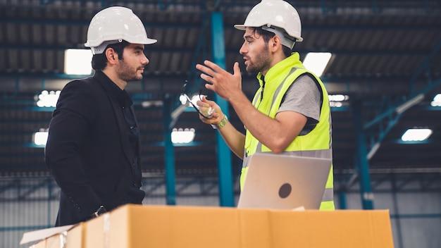 두 명의 공장 근로자가 공장에서 제조 계획에 대해 논의하고 있습니다. 산업 및 엔지니어링 개념.