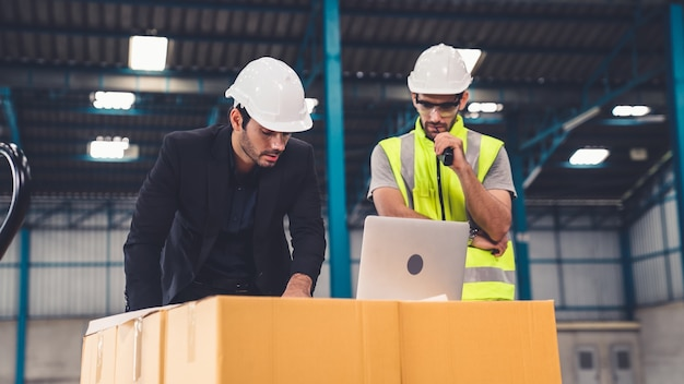 Двое заводских рабочих работают и обсуждают производственный план на заводе. промышленно-инженерная концепция.