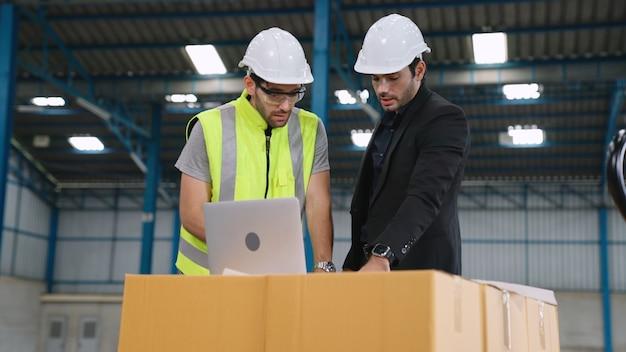 Двое заводских рабочих работают и обсуждают производственный план на заводе.