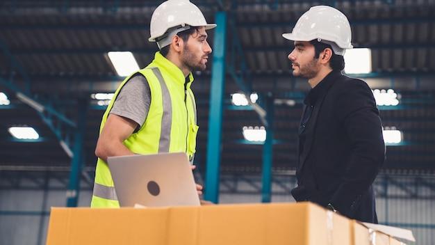 工場で働いて製造計画について話し合っている2人の工場労働者。