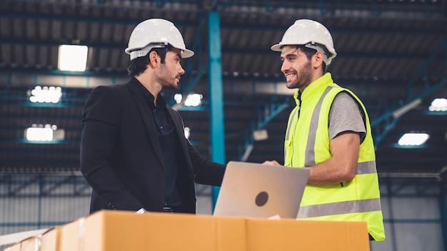 두 명의 공장 근로자가 공장에서 제조 계획에 대해 논의하고 있습니다.