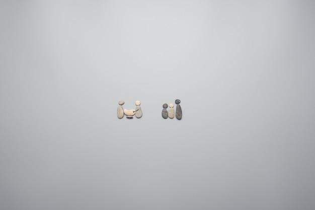 小石で作られた2つの家族単位。灰色の背景の上に、コピースペースがあります。