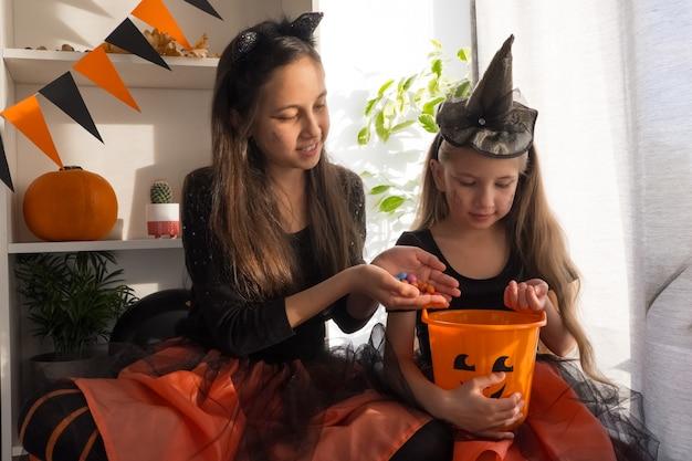 ハロウィーンの魔女の衣装を着た10歳と7歳の2人のファニーガール姉妹がホーリーを祝う