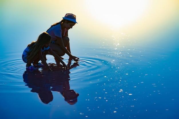 아름답고 투명한 소금 호수에서 특이한 의상을 입은 환상적으로 아름다운 두 소녀가 반짝이는 표면에서 무언가를 찾고 있습니다