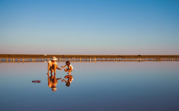 아름다운 투명한 소금 호수에 특이한 의상을 입은 두 명의 환상적으로 아름다운 소녀가 반짝이는 표면에서 무언가를 찾고 있습니다.