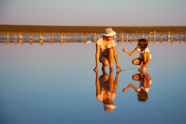 아름다운 투명한 호수에 있는 환상적으로 아름다운 두 소녀가 반짝이는 표면에서 무언가를 찾고 있습니다