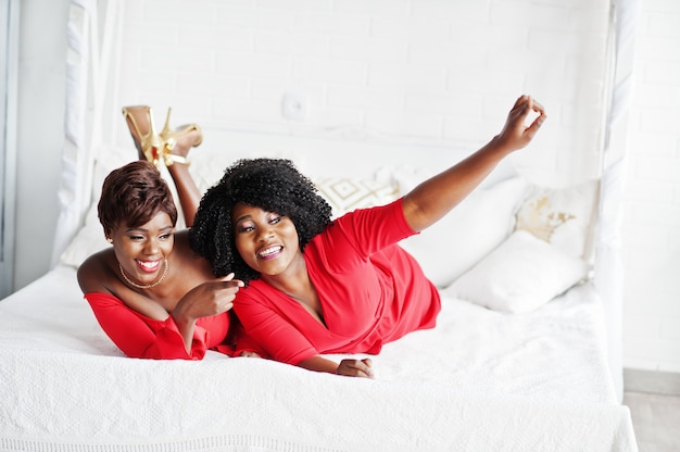 Two fashion african american models in red beauty dress and golden high heels, sexy womans posing evening gown lie on the bed.