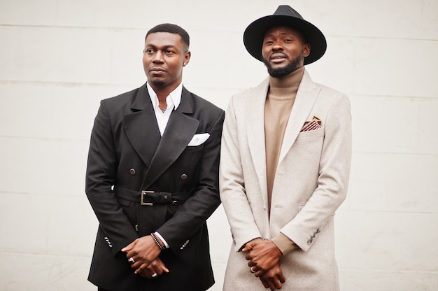 2人のファッション黒人男性。アフリカ系アメリカ人の男性モデルのファッショナブルな肖像画。スーツ、コート、帽子を着用してください。