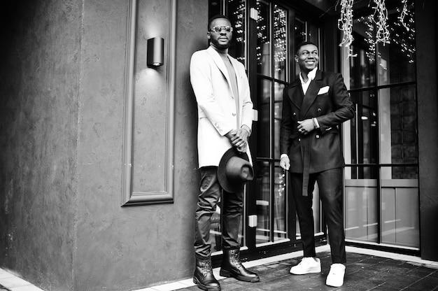 2人のファッション黒人男性が花輪のある家に対してポーズをとります。アフリカ系アメリカ人の男性モデルのファッショナブルな肖像画。スーツ、コート、帽子を着用してください。