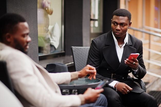 携帯電話で屋外に座っている2人のファッション黒人男性。アフリカ系アメリカ人の男性モデルのファッショナブルな肖像画。スーツ、コート、帽子を着用してください。