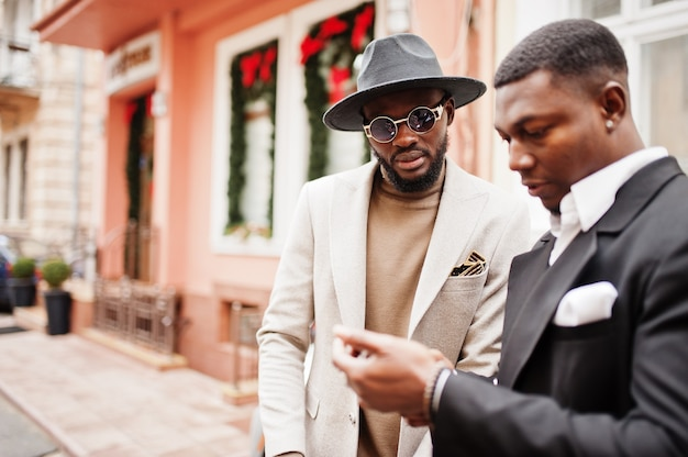2人のファッション黒人男性がビジネスカーの近くに立って携帯電話を見ています。アフリカ系アメリカ人の男性モデルのファッショナブルな肖像画。スーツ、コート、帽子を着用してください。