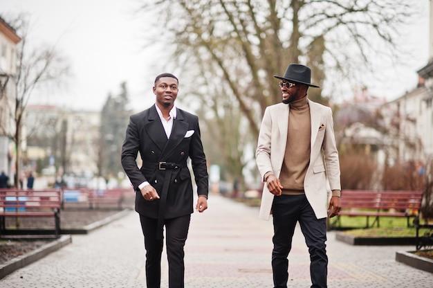 通りを歩いている2人のファッション黒人男性。アフリカ系アメリカ人の男性モデルのファッショナブルな肖像画。スーツ、コート、帽子を着用してください。