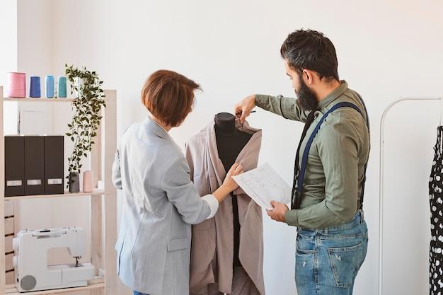 Due stilisti in atelier con abito a forma