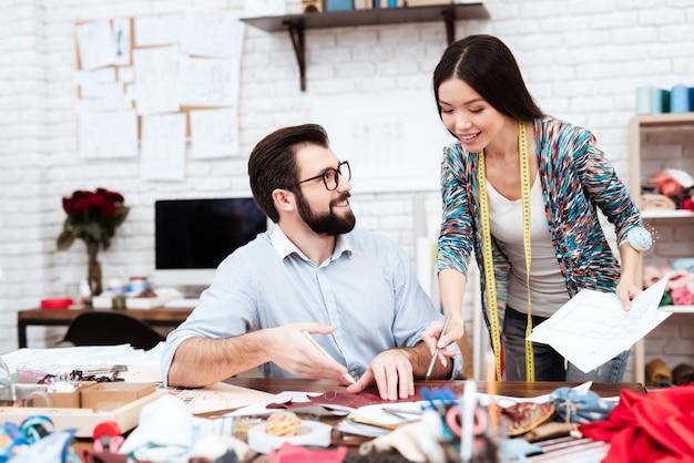 革に切り抜きを作る2人のファッションデザイナー。