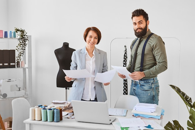 Due stilisti in posa in atelier con piani di linee di abbigliamento