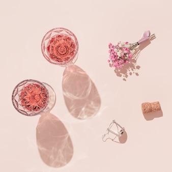 Два модных бокала розового вина и небольшой букет цветов на пастельно-розовом
