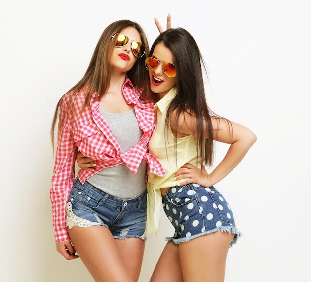 Две модные смеющиеся нарисованные подруги обнимаются и веселятся.