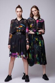 黒のロングスカートとシャツドレススニーカーの2つのファッションモデル美しい若い女性の背景