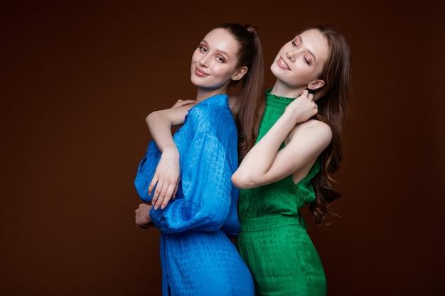 青いドレスシューズ緑のジャンプスーツスニーカーの2つのファッションモデル美しい若い女性スタジオショット