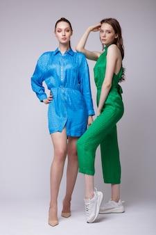 短い青いドレスシューズ緑のジャンプスーツスニーカーの2つのファッションモデル美しい若い女性