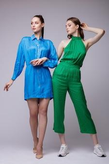 短い青いドレスシューズ緑のジャンプスーツスニーカーの2つのファッションモデル美しい若い女性 Premium写真