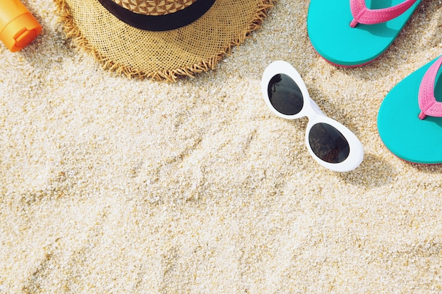 Two fashion sunglasses close up on the beach sand in summer.