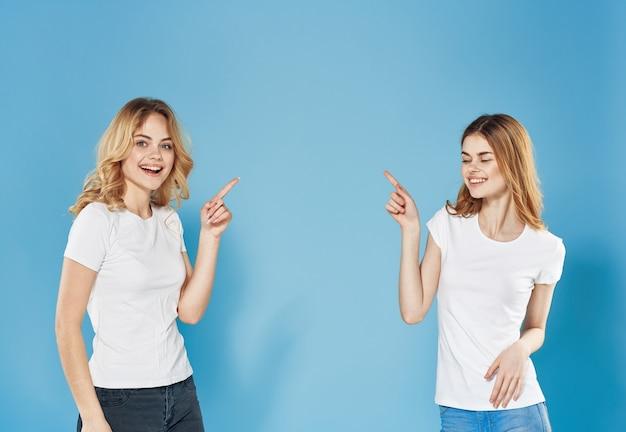2つのファッションの女性のコミュニケーションの感情は不満の青い背景を対立します